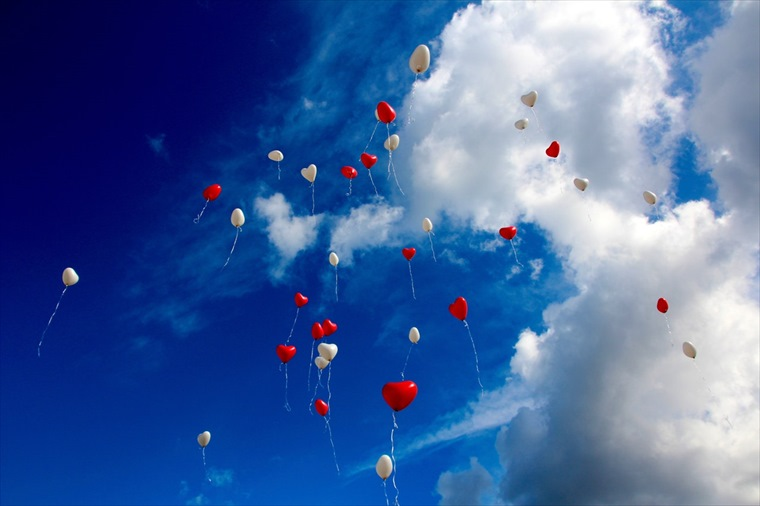 空に高く飛んでいく赤と白の風船